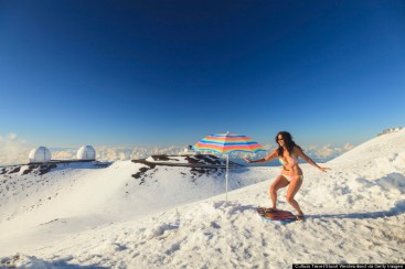 Woman in bikini surfing in snow